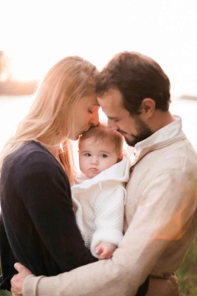 photographe de famille : portrait de famille, lors d'un câlin avec la maman, le papa, et leur fille, photo lumineuse au bord de garonne, séance photo automne