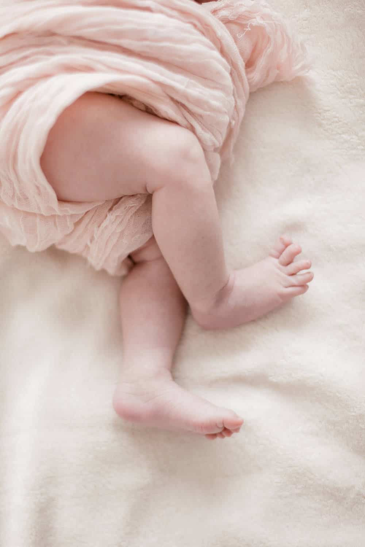 photographe de nouveau-né, détail de petits pieds, enveloppés dans une gaze rose pale