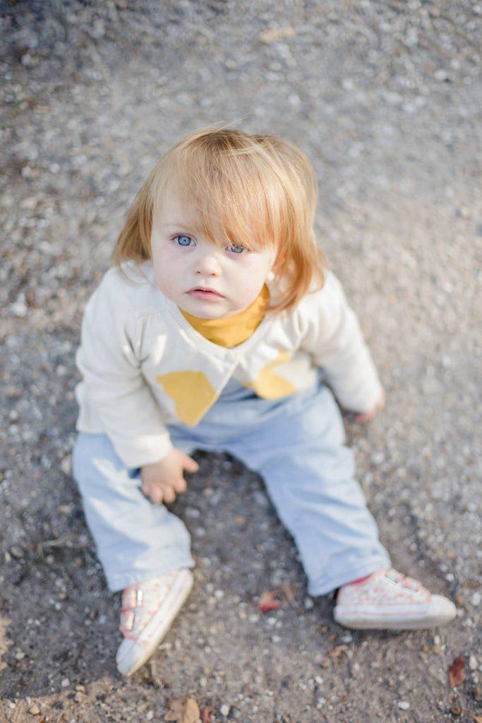 Portrait d'une enfant, une petite fille d'1 an assise dans un parc à Bordeaux, photo lumineuse