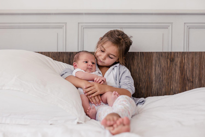 photographe naissance : photo d'une grande soeur tenant son frère, bébé, dans les bras