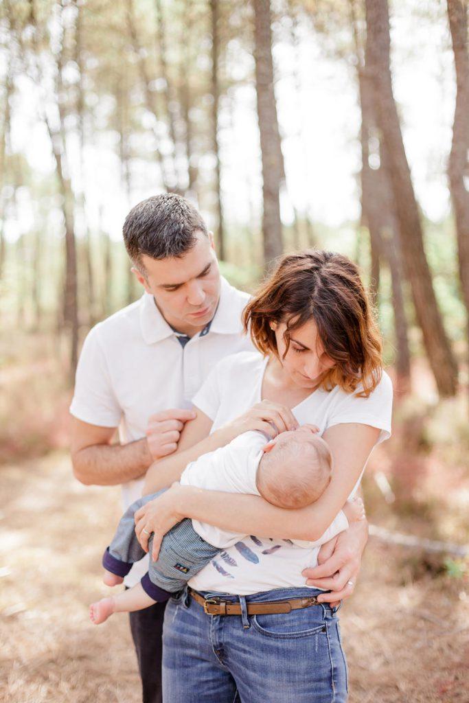 Séance photo en exterieur en famille, bébé de 3 mois, dans les bras de ses parents, dans une forêt à Bordeaux