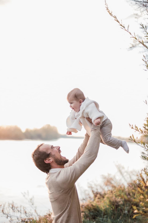 séance photo famille : un papa avec sa fille joue ensemble avec beaucoup de complicité