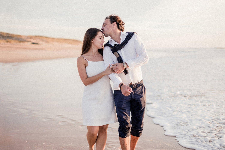 photo d'une photographe de mariage, d'un couple très amoureux marchant sur une plage du cap ferret, ou d'arcachon ou du pays basque, avec beaucoup d'emotion et de sentiments