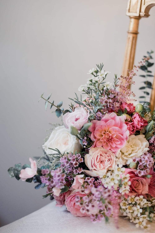 Photographie de mariage : sur une chaise élégante, un bouquet de mariée aux couleurs rose pale, pastels, blush, réalisé par la fleuriste Avril-Mai à Bordeaux, lors d'un mariage d'automne