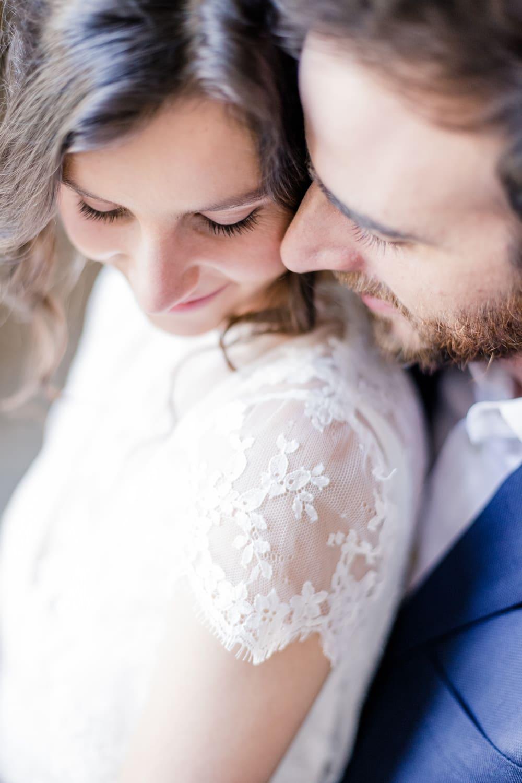 Emotion de deux mariés qui s'enlacent après leur mariage romantique ; la mariée porte une robe en dentelle de la créatrice Confidentiel Création à Bordeaux