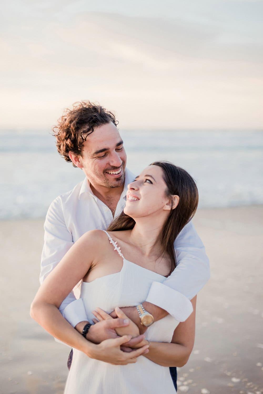 Photographe de mariage : photo d'un couple d'amoureux, s'enlaçant, avec un regard de complicité et d'amour, prise lors d'une séance engagement, appelée aussi Love Session, à la plage, au Cap Ferret, ou à Arcachon, ou au Pays Basque