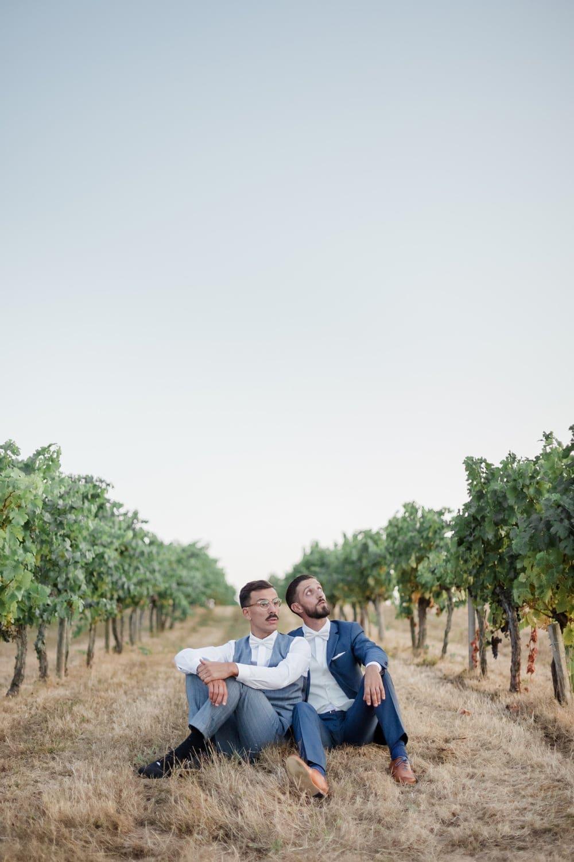 Photographe de mariage pour tous gay homosexuel : deux hommes mariés sont côte à côte assis au milieu des vignes du bordelais