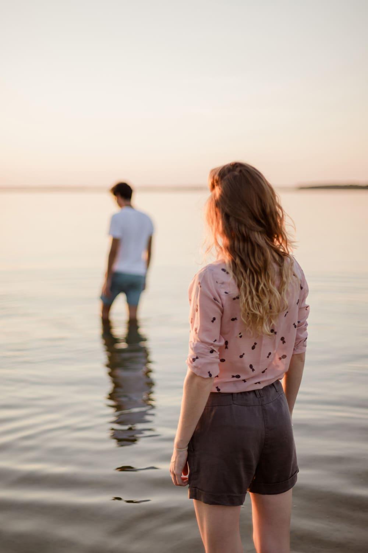 Photographe de mariage : jeune femme rousse qui regarde son homme lors d'une love session ou séance engagement ou séance photo couple au bord d'un lac à Bordeaux, ou au Pays Basque, ou dans les Landes, ou en Dordogne