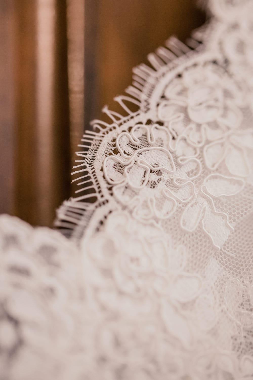 Détail de la dentelle de calais d'une robe de mariée pris en photo par la photographe de mariage à Bordeaux