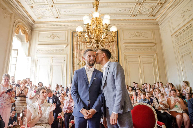 Photographe de mariage à la mairie de Bordeaux : mariage pour tous gay homosexuel à Bordeaux, cérémonie civil ou l'un des marié embrasse l'autre tendrement sur la joue devant amis et familles