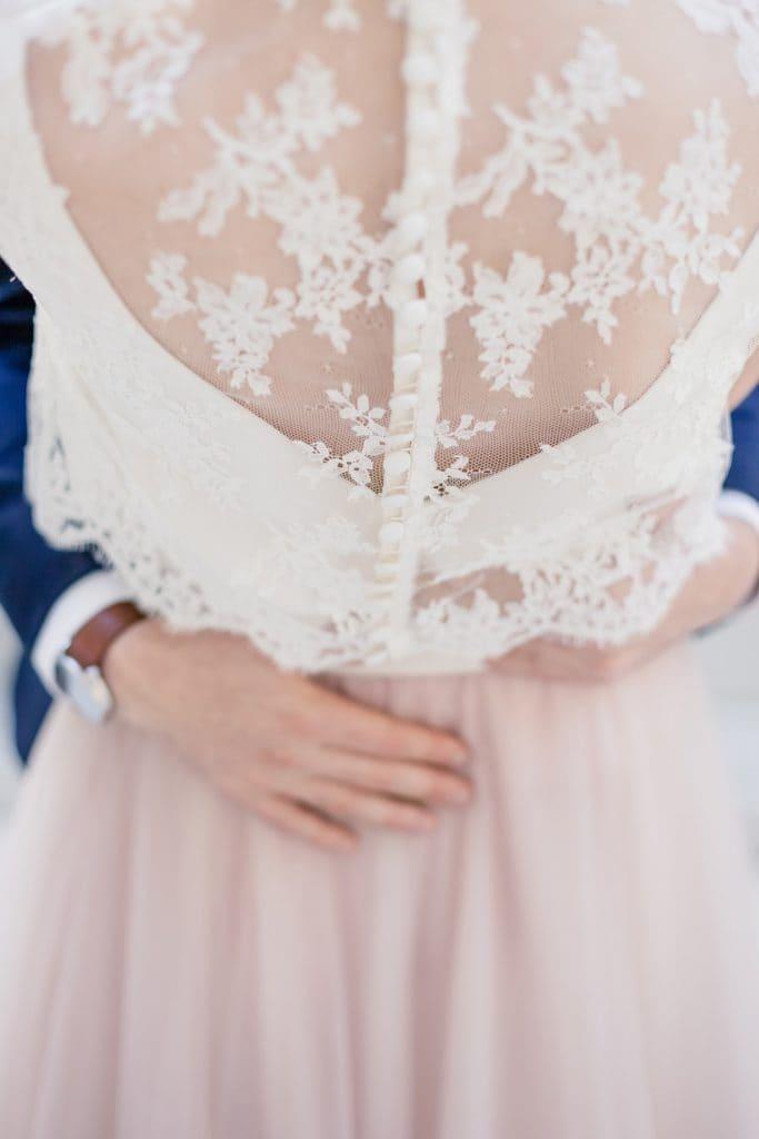 Photographe de mariage romantique à Bordeaux : détail de dentelle de calais sur une robe de mariée de créatrice signée Confidentiel Création