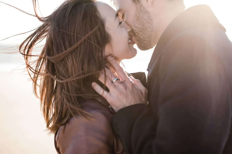 photo lumineuse de la tendresse d'un couple d'amoureux lors d'une séance engagement, une love session à la plage, sur Arcachon, à l'océan au Cap Ferret ou sur la côte basque