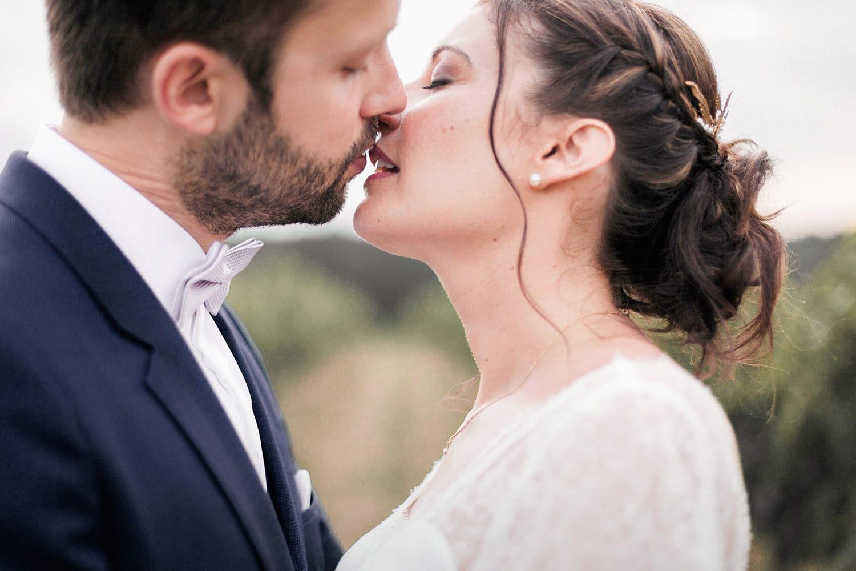 photographe mariage : couple de mariés amoureux, s'embrassant tendrement, au château de la Loubière à Bordeaux, Bonnetan ; la mariée porte une robe Elsa Gary