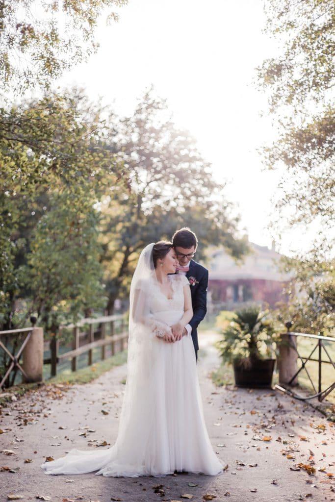 photographe fine art mariage : couple de mariés tendrement enlacés et amoureux sur une photo lumineuse en contre-jour