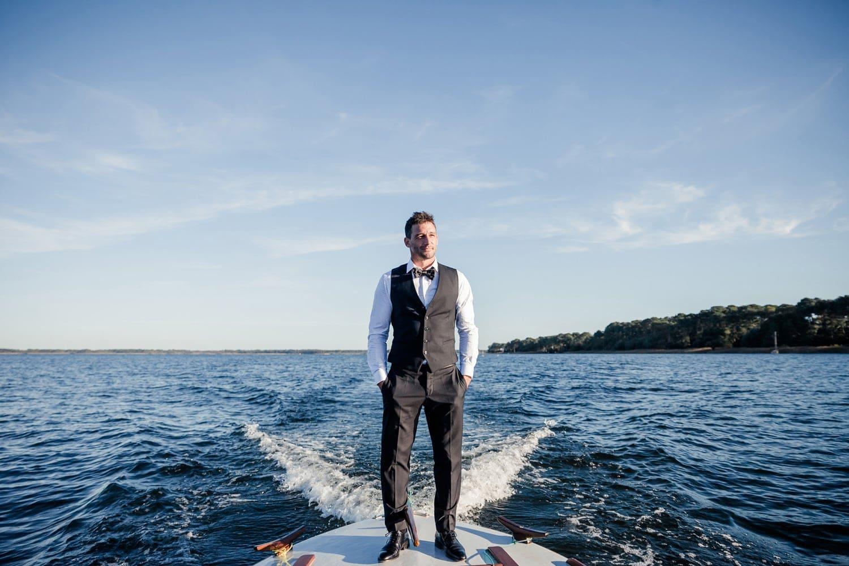 portrait cool d'un marié sur un bateau au milieu de l'océan, photo de mariage à la plage