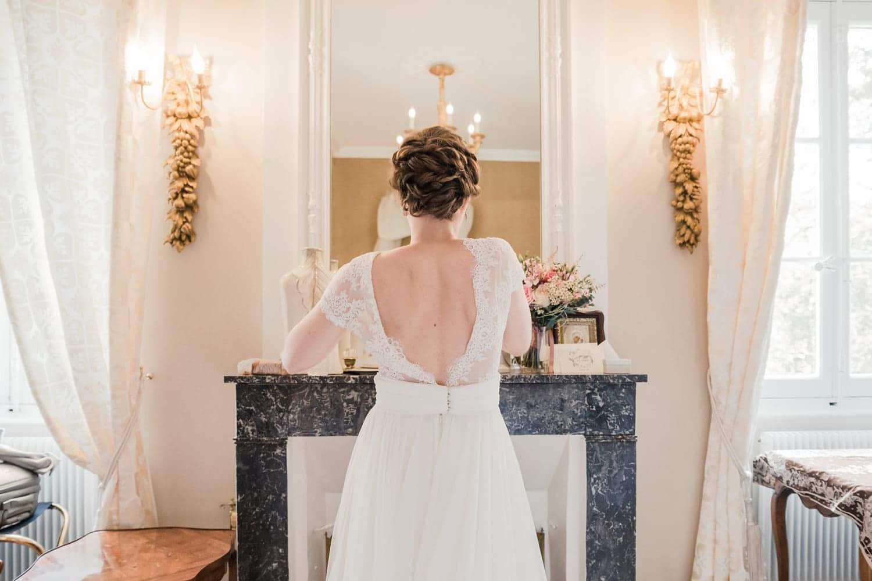 Photographe mariage Bordeaux, la mariée dans sa belle robe dos nu en dentelle pendant les préparatifs