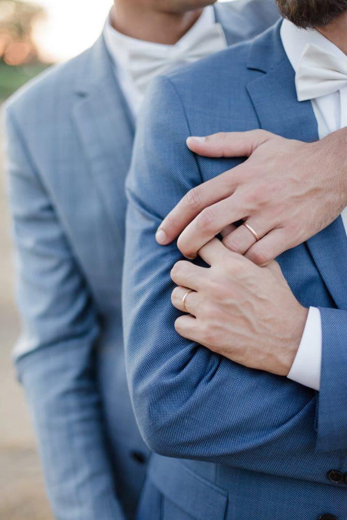 Photographe de mariage pour tous gay homosexuel à Bordeaux : deux hommes mariés se tiennent la main, dans leurs beaux costumes de mariés