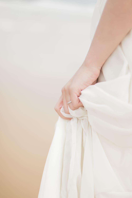 détail de robe de mariée en soie, avec bague de fiançailles ou alliance, sur la plage lors d'un day after avec la photographe