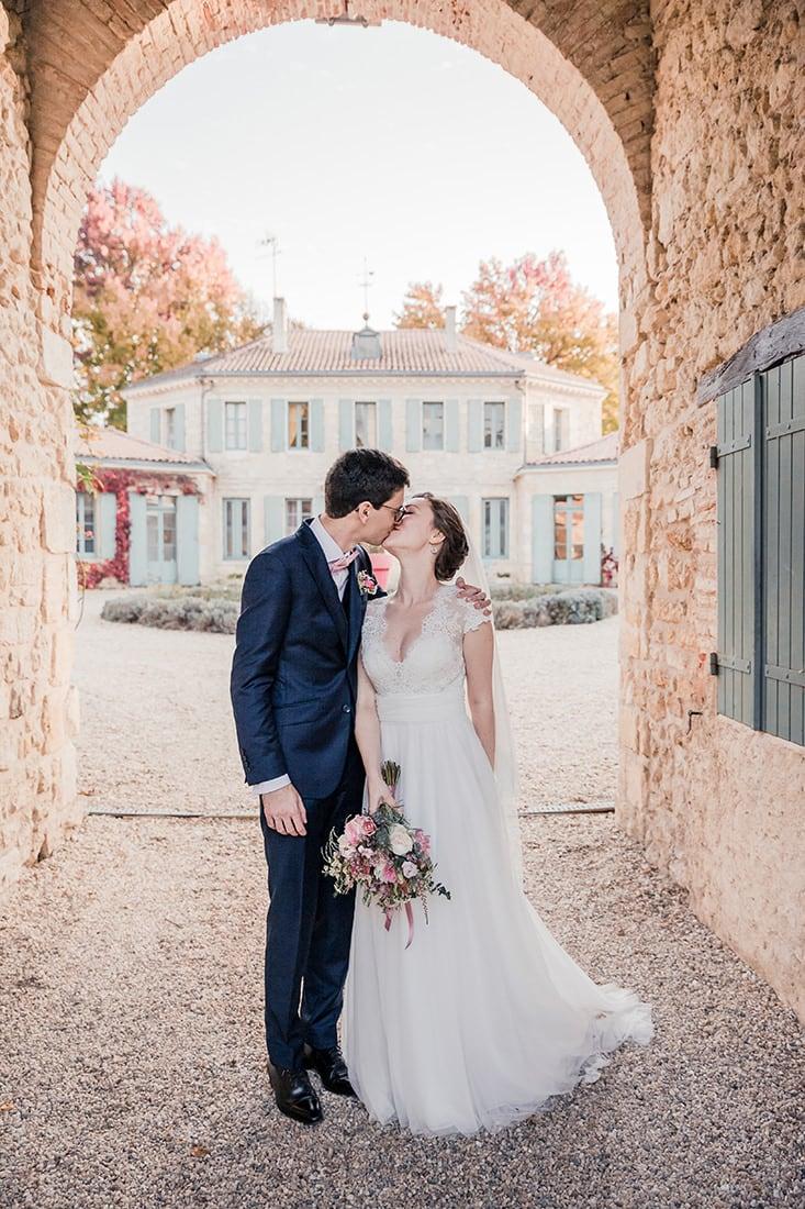 Photographe de mariage : photo d'un couple de mariés amoureux qui s'embrasse sour un porche dans un château à Bordeaux ou en Dordogne ou au Pays Basque