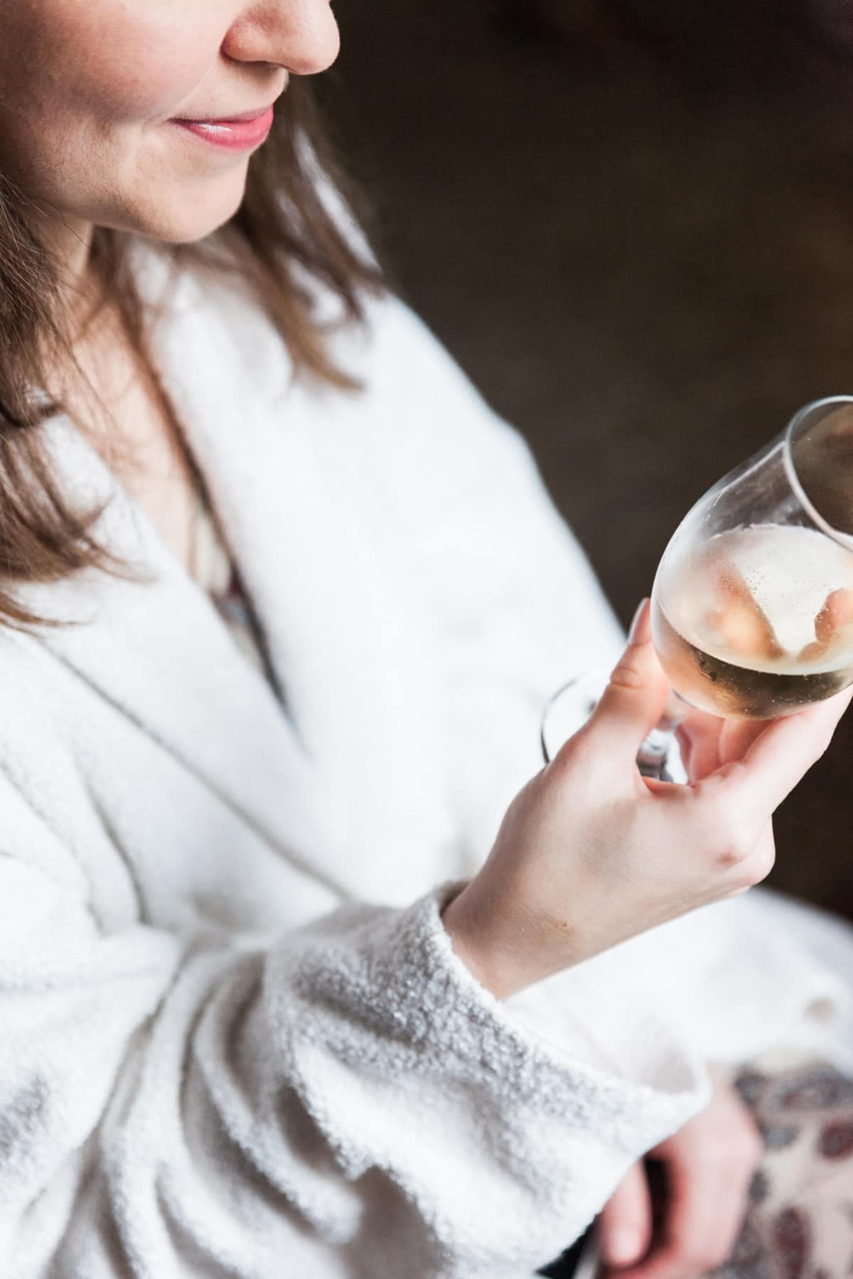 La mariée boit une coupe de champagne pendant les préparatifs
