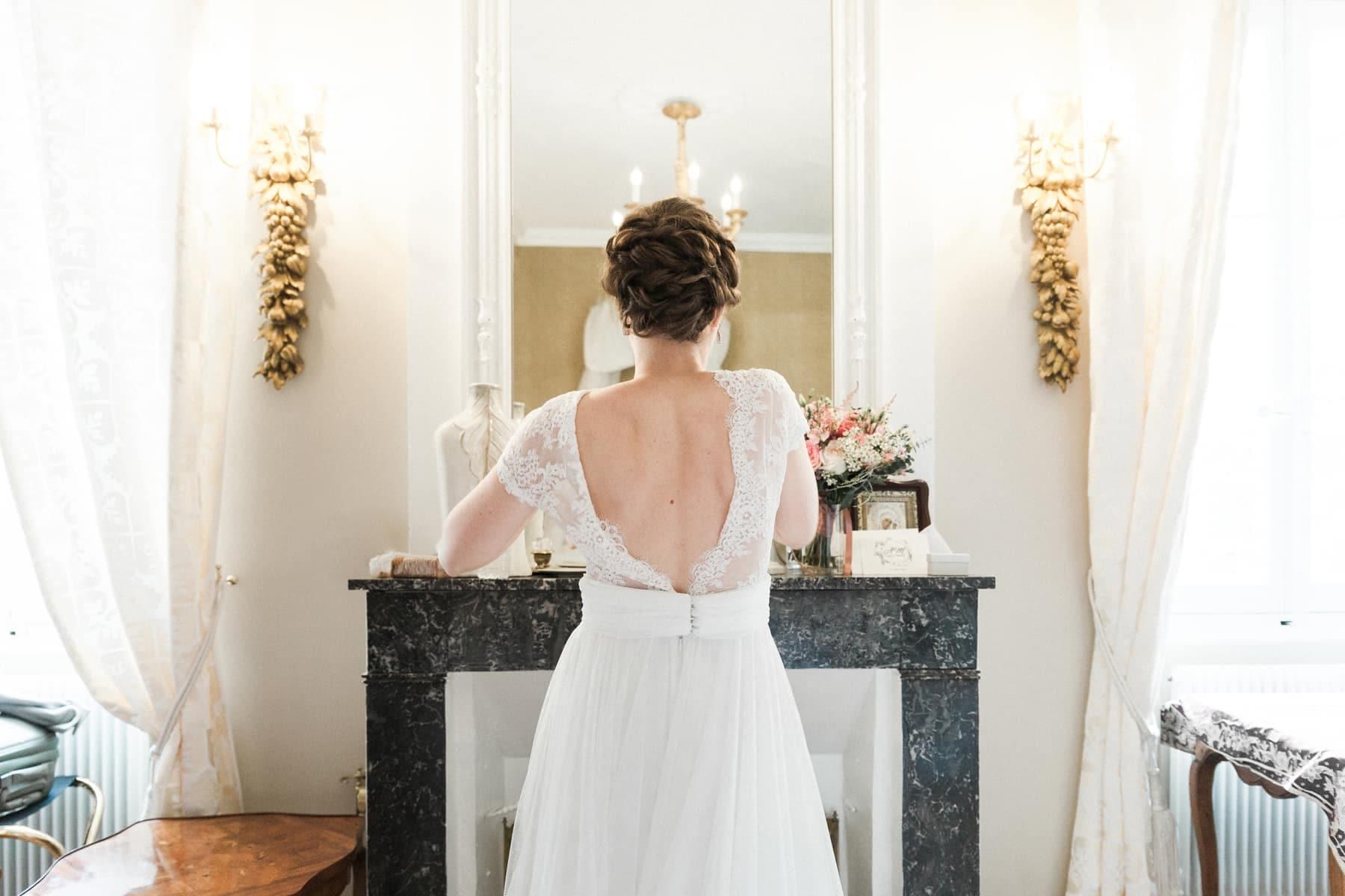 Château de l'Isle Médoc : la mariée pendant les préparatifs réajuste sa robe de mariée