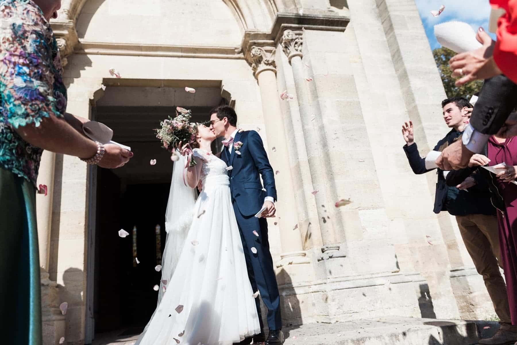 Photographe de Mariage à Bordeaux : Sortie des mariés, confettis et paillettes à l'église de Saint Jean d'Illac