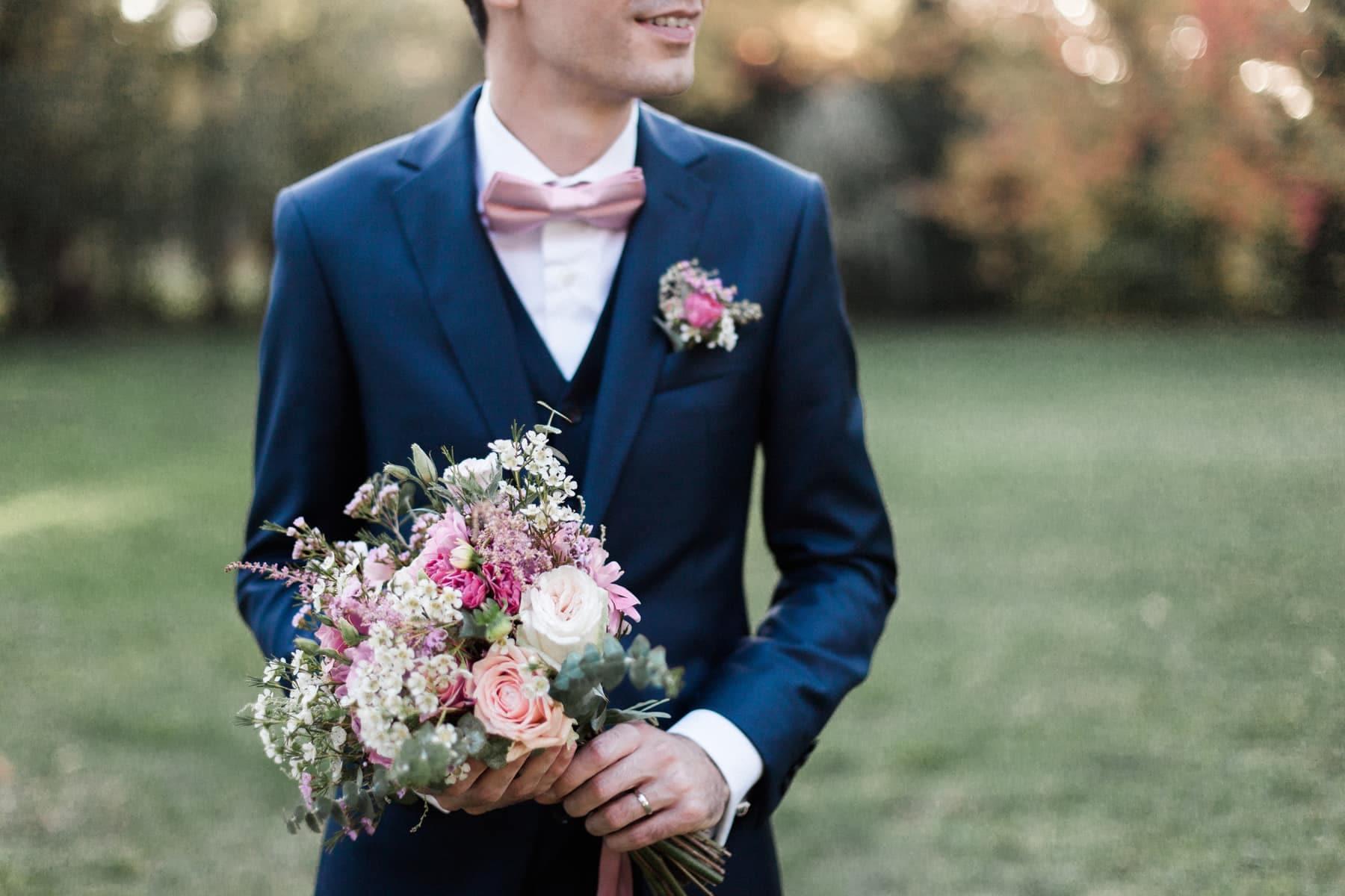 Mariage franco russe : portrait serré du bouquet de mariée rose blush signé Avril-Mai dans les mains du marié