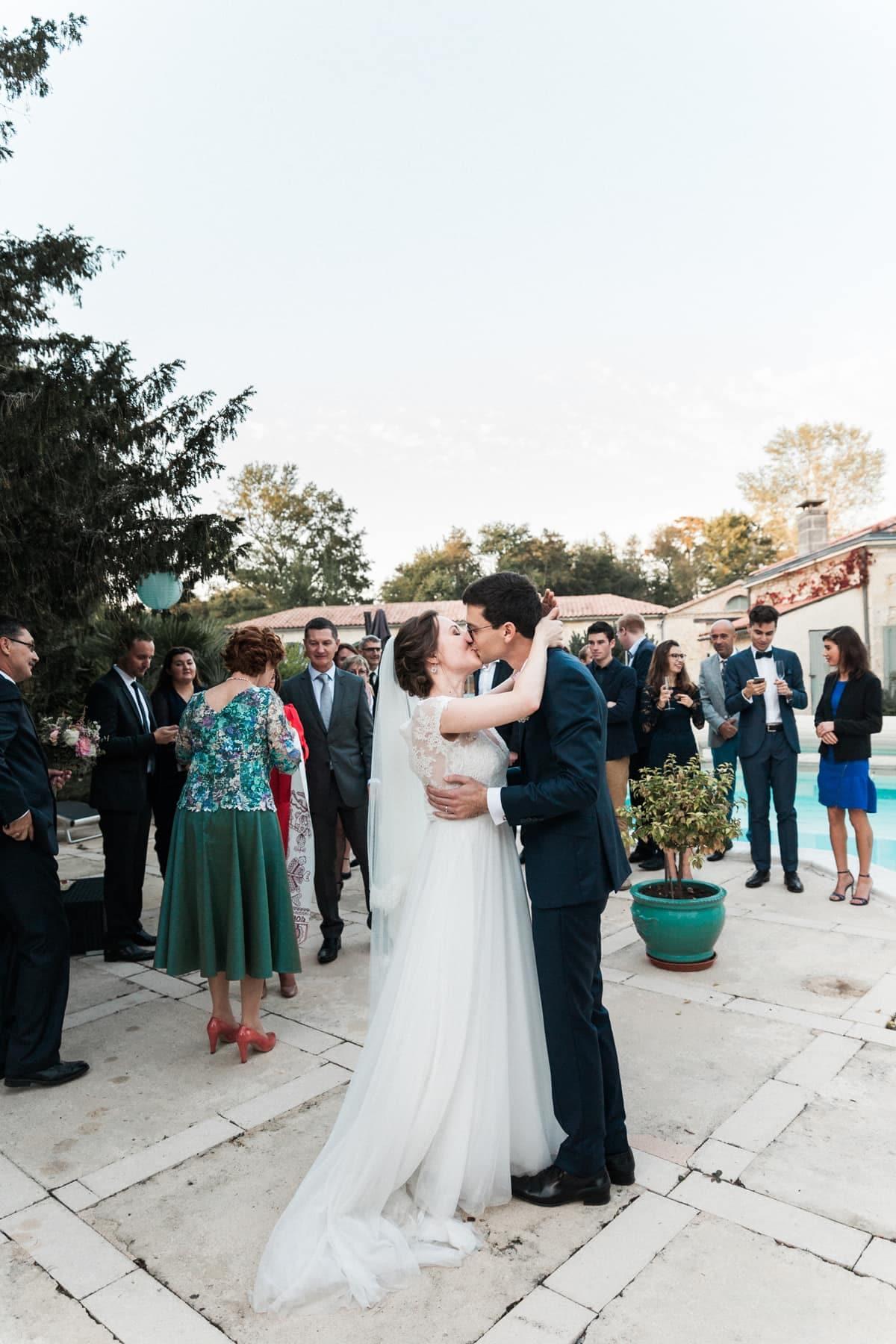 Mariage intimiste à Bordeaux : les mariés s'embrassent au milieu des invités