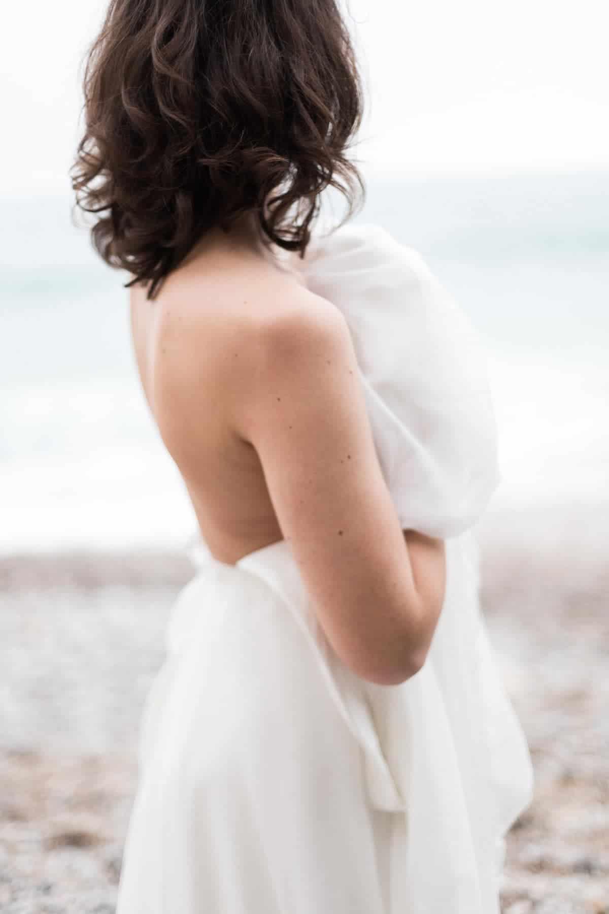 Mariée de dos, sensuelle et romantique, sur la plage d'Etretat