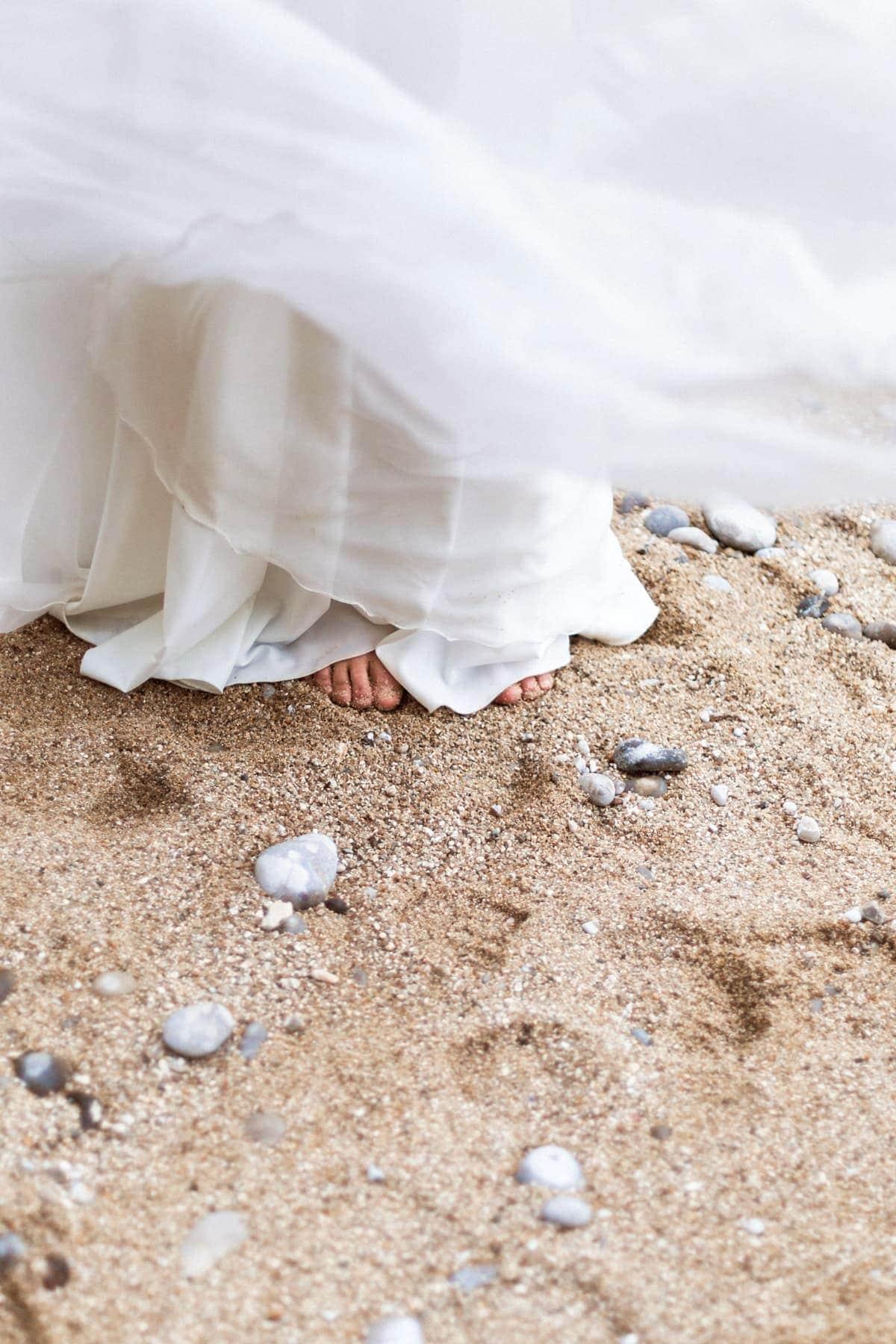 photo de détail, les pieds dans le sable pour un mariage à la plage