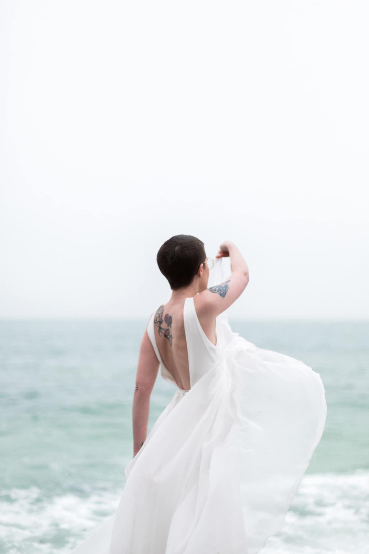 Photographe de mariage sur la plage : la mariée danse avec sa robe