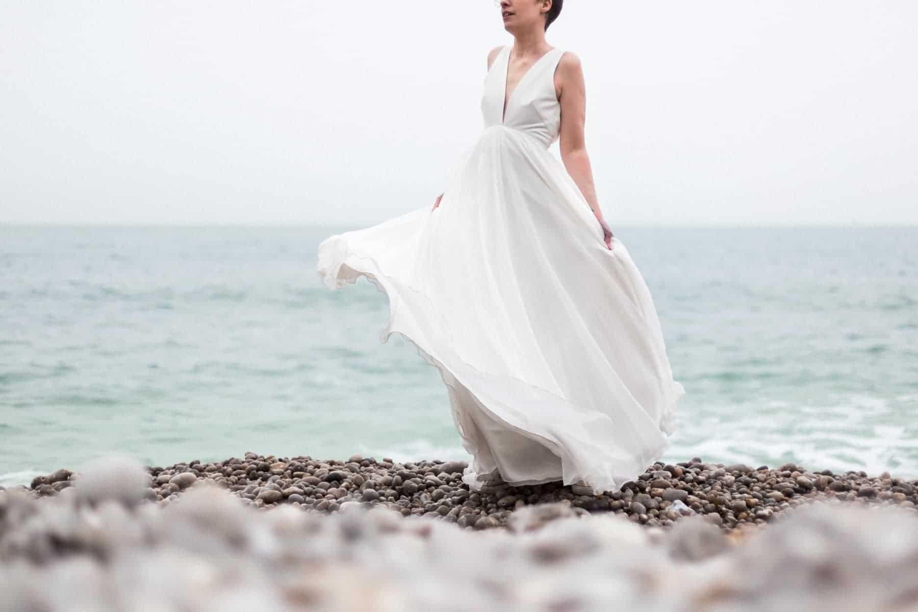 La mariée danse sur la plage d'Etretat en Normandie avec sa robe de créatrice