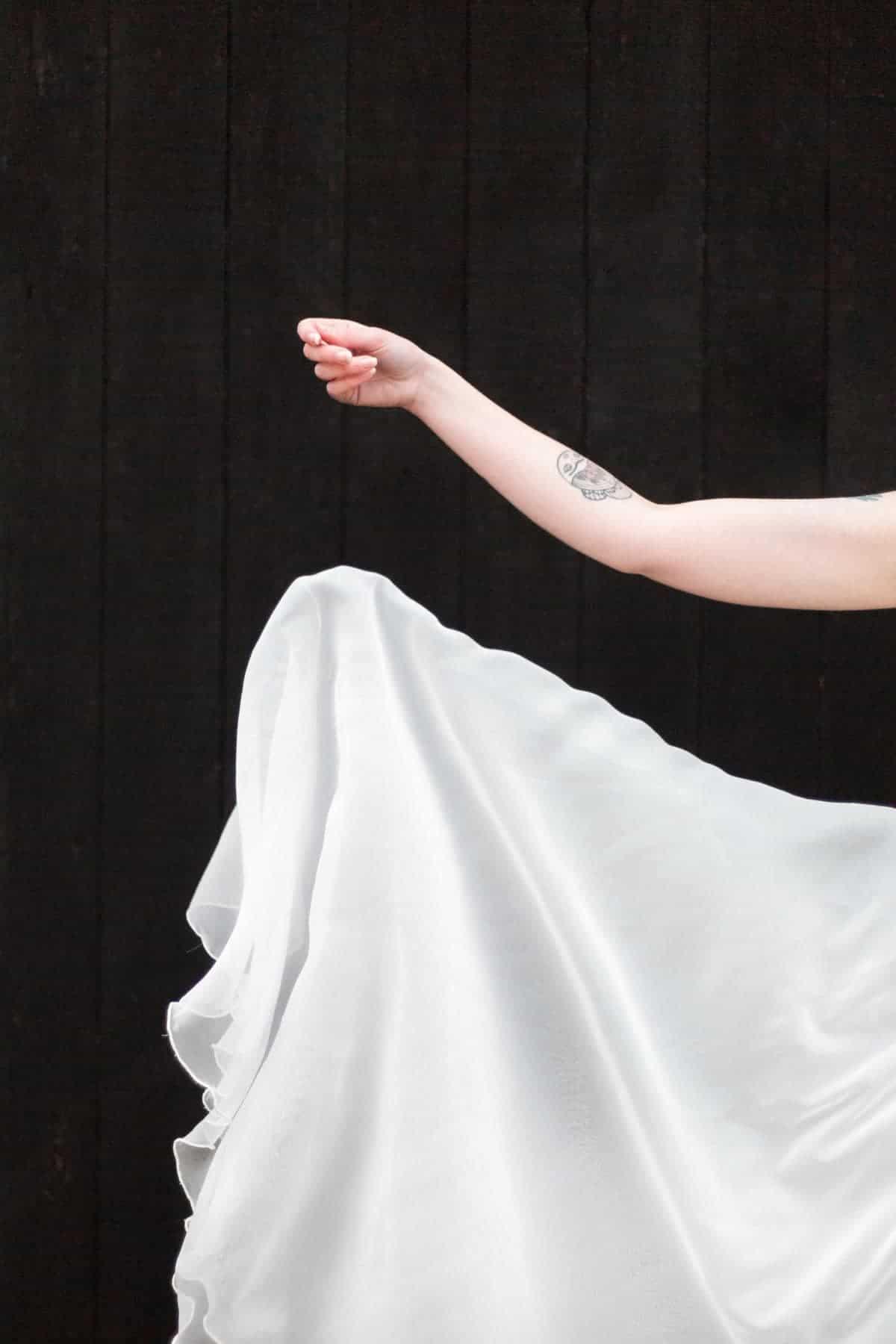 bras de la mariée jouant avec sa robe de mariée