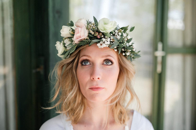 portrait de la mariée maquillée et coiffée, avec une couronne de fleurs