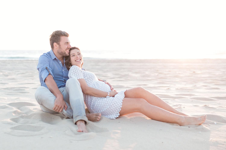 le couple d'amoureux assis dans le sable profitant du coucher de soleil