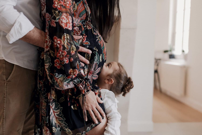 bisou d'une enfant sur le ventre de sa maman