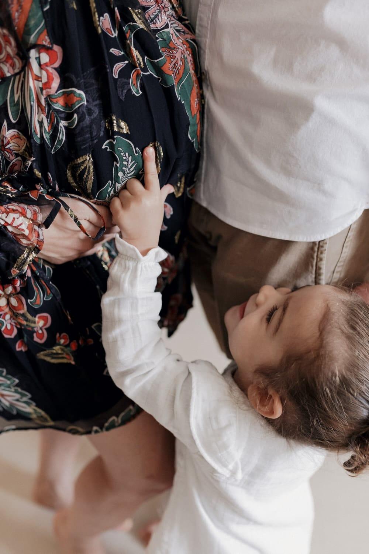 la petite fille montre le ventre de maman avec bébé à l'interieur